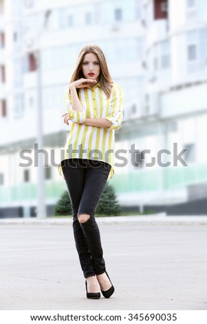 Beautiful young girl posing on city street