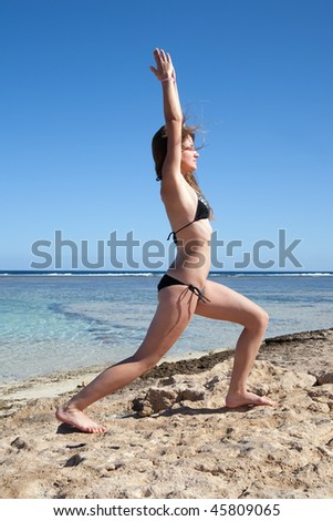 Beautiful young girl practicing yoga  against sea