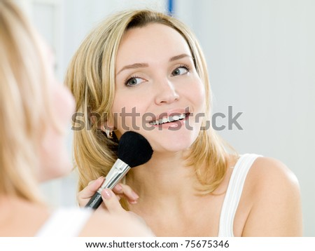 Beautiful young girl puts powder on the face by means of a brush for a make-up - indoors - stock photo
