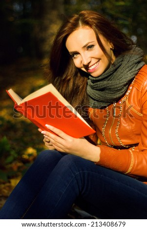 beautiful young girl reading a book in the park - stock photo