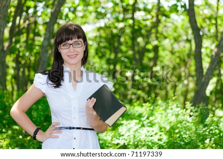 beautiful young girl reading a book on the nature