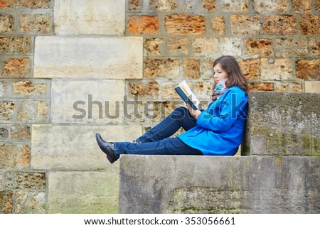 Beautiful young girl reading a book on the Seine embankment in Paris