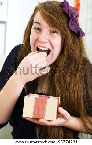 Beautiful young girl receives a gift, surprised - stock photo