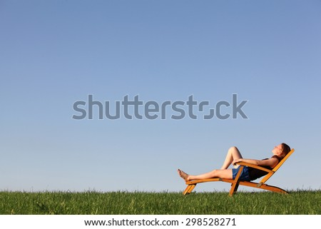 Beautiful young girl relaxes on a deckchair in a meadow - stock photo