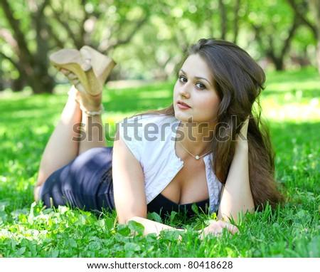 beautiful young girl relaxing in summer green park - stock photo