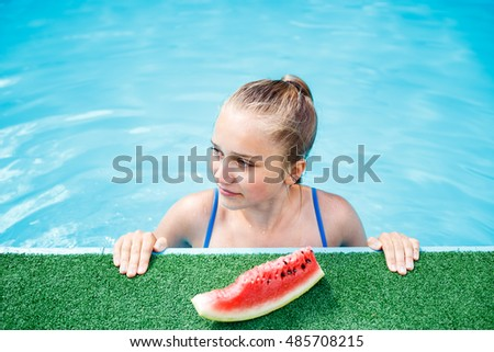 Beautiful young girl relaxing in the swimming pool with slice of watermelon. Overhead view