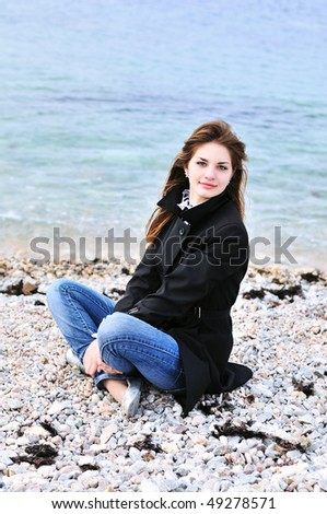 Beautiful young girl relaxing near the sea in spring time