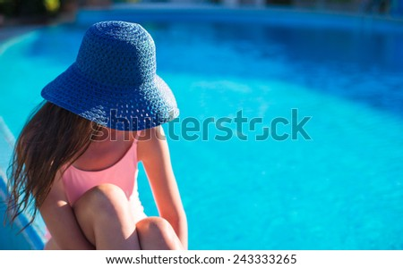 Beautiful young girl relaxing near the swimming pool - stock photo