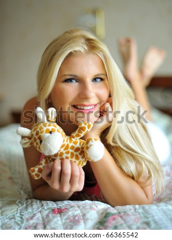 Beautiful young girl relaxing on the bed in her room indoors with a toy - stock photo