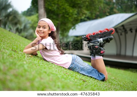 Beautiful young girl resting after rollerblading in the park - stock photo