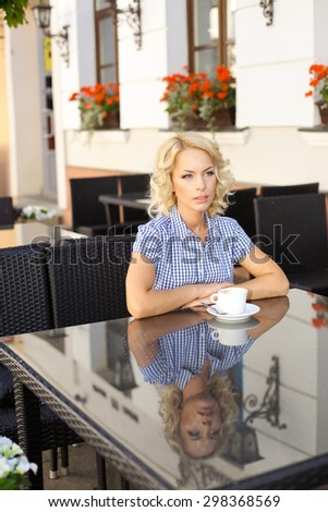 beautiful young girl resting in a cafe. attractive blond model sitting with a cup of coffee in an outdoor cafe of the European city