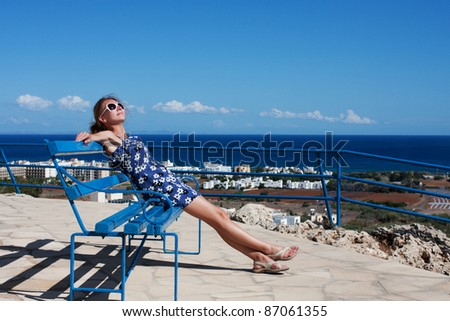 Beautiful young girl resting on a bench - stock photo