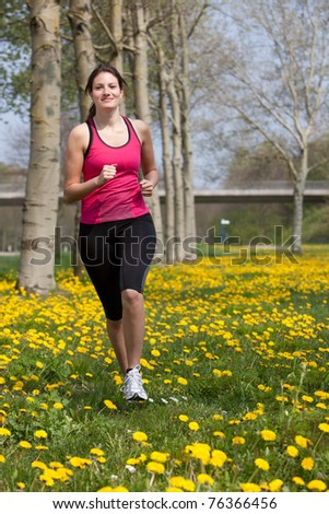 Beautiful young girl running in a field of dandelions