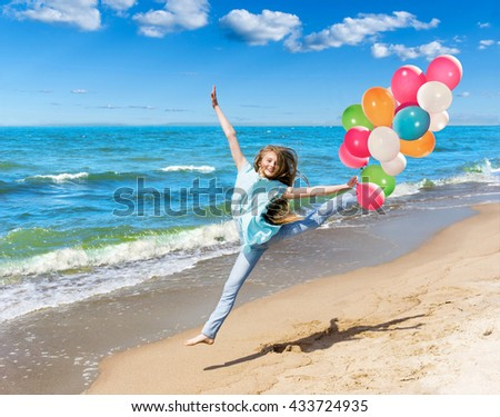 Beautiful young girl running on the beach with balloons - stock photo