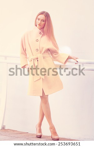 Beautiful young girl showing fashionable yellow coat on a light background wall - stock photo