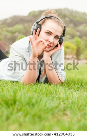 Beautiful young girl showing ok gesture while lying on grass and listening music on headphones - stock photo
