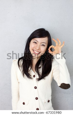 beautiful young girl showing OK sign - stock photo