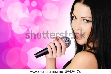 Beautiful young girl singing in microphone - stock photo