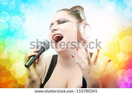 Beautiful young girl singing in microphone on color abstract background