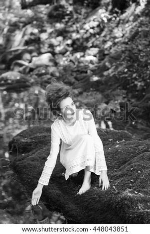 beautiful young girl sitting beside a stream