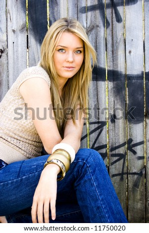 beautiful young girl sitting in front of a graffiti fence - stock photo