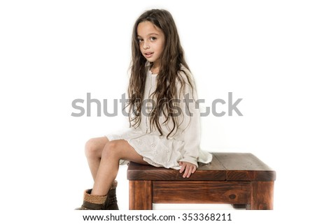 beautiful young girl sitting on a small wooden table isolate - stock photo