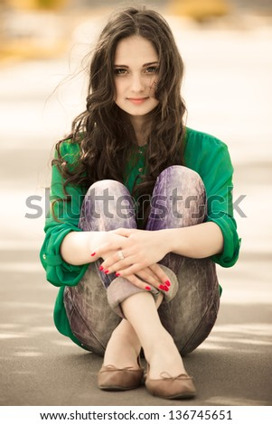 beautiful young girl sitting on a way - stock photo
