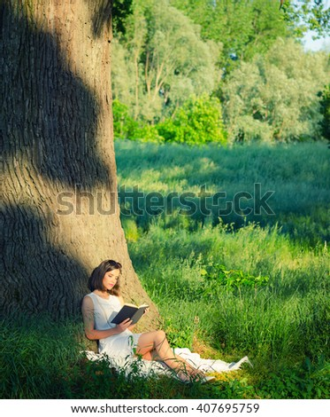 Beautiful young girl sitting on blanket under giant oak and reading book on sunny summer day. - stock photo