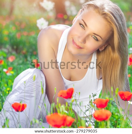 Beautiful young girl sitting on fresh poppy flower field, having fun in fresh floral garden, enjoying amazing spring time sunny day - stock photo