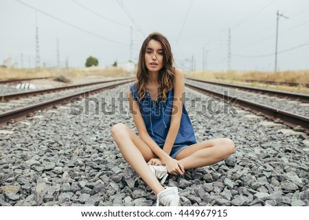 Beautiful young girl sitting on the railway.