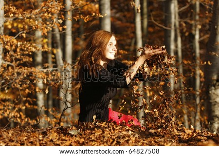 Beautiful young girl sitting through autumn leaves in the middle of the forest, meditating and relaxing