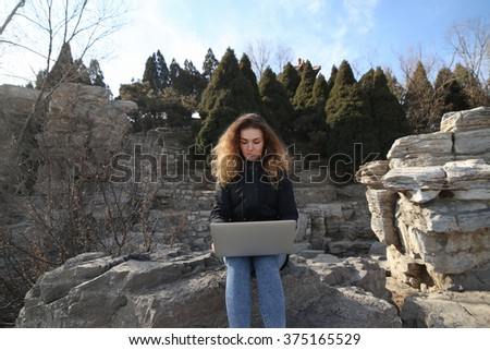 Beautiful young girl sitting with a laptop in the park on a background of mountains. The possibilities are endless on the Internet to work, learn, communicate. - stock photo