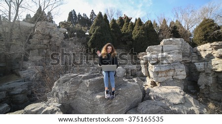 Beautiful young girl sitting with a laptop in the park on a background of mountains. The possibilities are endless on the Internet to work, learn, communicate. Speak with family online. - stock photo