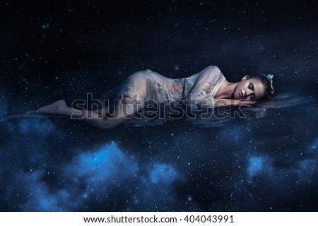 Beautiful young girl sleeps in the arms of space among the stars , fantaskicheskaya fotoshoot , fashionable toning , creative color - stock photo