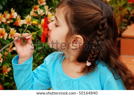 beautiful young girl smelling a red flower - stock photo