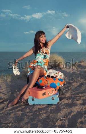 Beautiful young girl smiling and waving a white hat. She sits on his colorful suitcases.