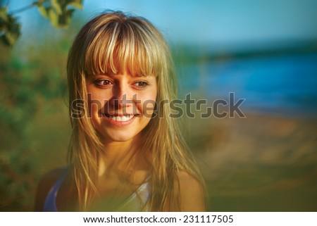 Beautiful young girl smiling. sunset light - stock photo