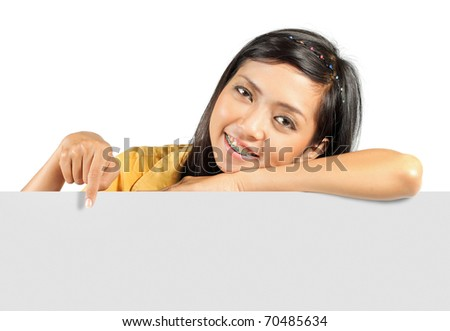 beautiful young girl smiling while holding a big blank card - stock photo