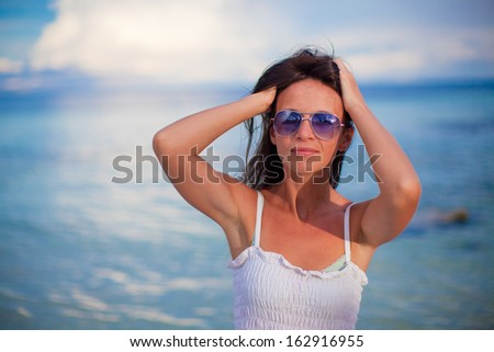 Beautiful young girl standing at beach and looking in camera