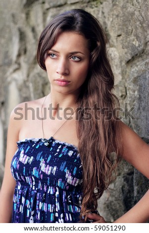 Beautiful young girl standing at the wall