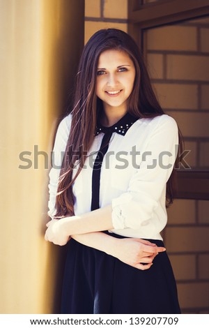 Beautiful young girl standing near the golden column - stock photo
