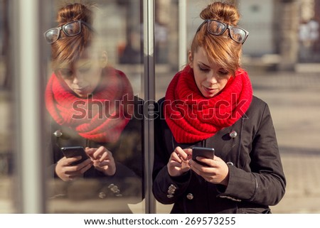 Beautiful young girl standing next to a shop window and typing a text message on her smart phone - stock photo