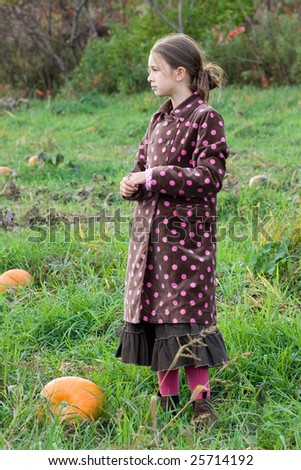 Beautiful young girl stands in a green pumpkin field - stock photo