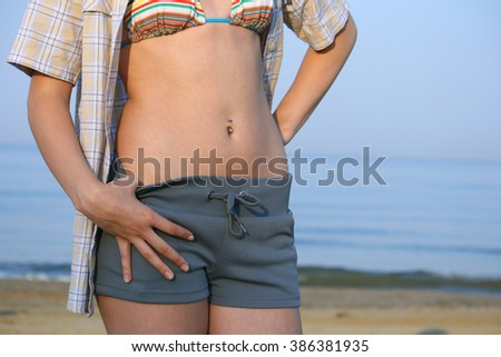 Beautiful young girl stomach. Shot taken at the beach against the sea.