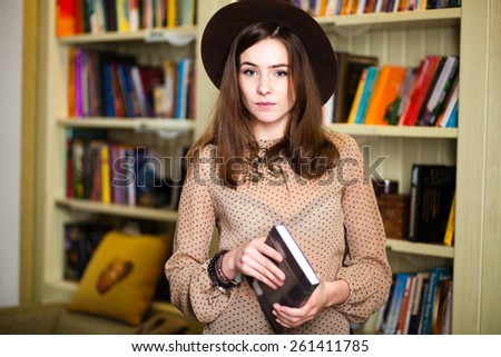 beautiful young girl student near the bookshelves in the library.   concept formation. University, School - stock photo