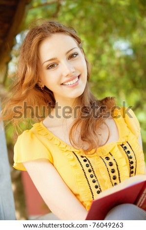 beautiful young girl-student read the book on a park bench on the background of green nature