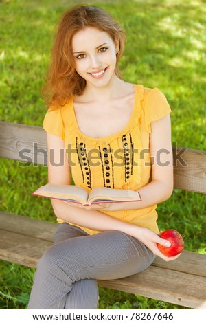 beautiful young girl-student read the book on a park bench with an apple in his hand on the background of green nature - stock photo