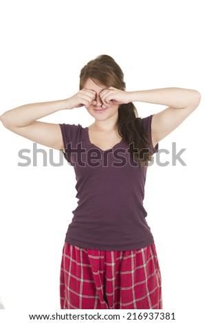 Beautiful young girl student teenager wearing purple pyjamas waking up rubbing eyes isolated on white - stock photo