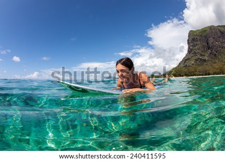beautiful young girl surfer swims in the clear waves. She rides in the Indian Ocean island of Mauritius - stock photo