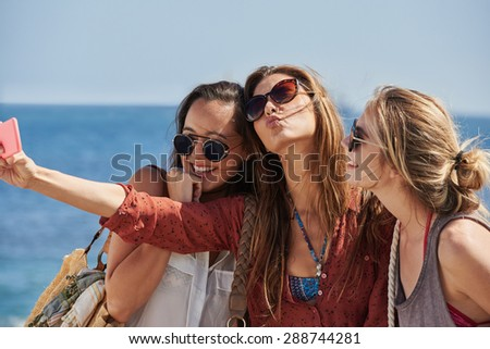 Beautiful young girl taking a selfie with her women friends by the sea smiling - stock photo